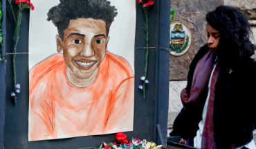 A woman who did not want to be identified holds a memorial display with a drawing of Antwon Rose II in front of the court house on the first day of the trial for Michael Rosfeld, a former police officer in East Pittsburgh, Pa., begins on Tuesday, March 19, 2019, in Pittsburgh. Rosfeld is charged with criminal homicide in the fatal shooting of Antwon Rose II as he fled during a traffic stop on June 19, 2018. (AP Photo/Keith Srakocic)