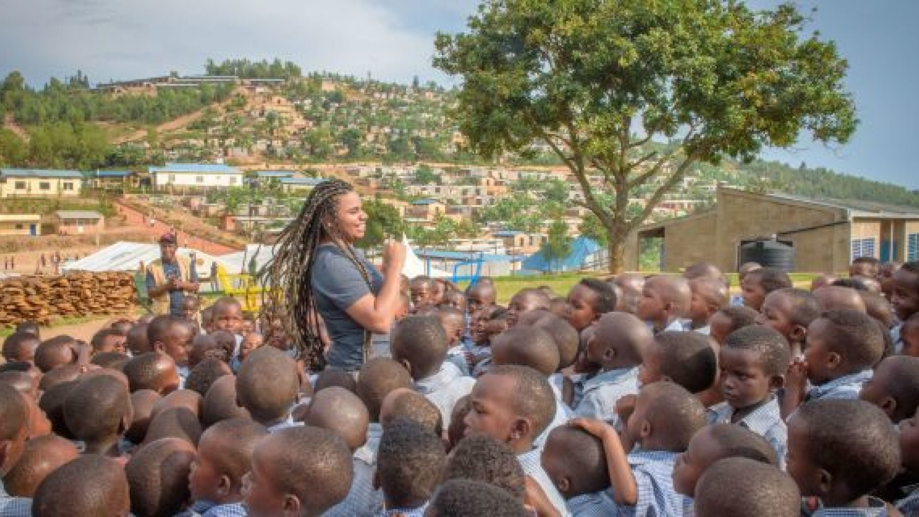 Wé McDonald visiting Rwanda with the Christian humanitarian agency World Vision, celebrating with a community receiving clean water for the first time and meeting children impacted by World Vision's work.