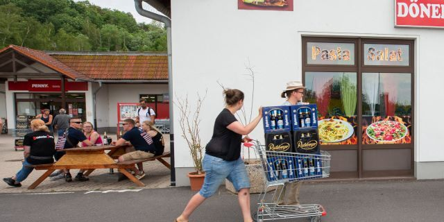 A woman and a man push a shopping cart with beer crates along the street near a local supermarket to protest the Shield and Sword Festival.  (Photo by Daniel Schäfer/picture alliance via Getty Images)