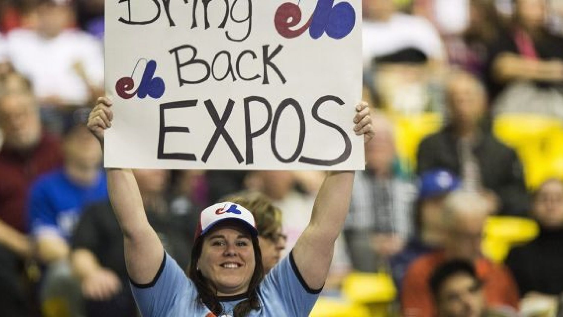 FILE - In this April 3, 2015, file photo, a fan holds up a sign during a pregame ceremony as the Toronto Blue Jays face the Cincinnati Reds in an exhibition baseball game in Montreal <a class=