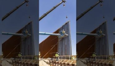 Workers install the first panels of the Calexico border wall project