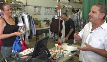 Matthew Porche (right) talks to his employees at his family-owned dry cleaners as they finish scanning customers