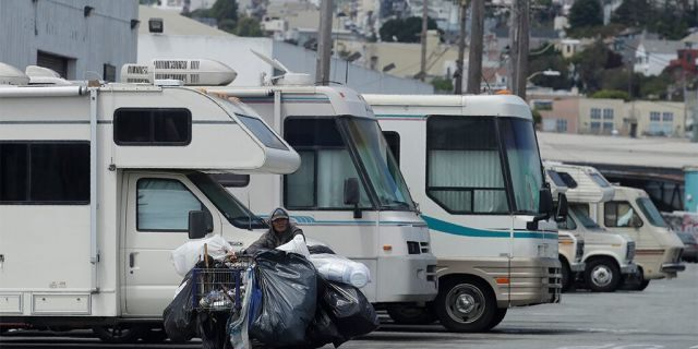 This Thursday, June 27, 2019, photo shows a person pushing a cart past parked RVs along a street in San Francisco. A federally mandated count of homeless in San Francisco increased 17% in two years, driven in part by a surge of people living in RVs and other vehicles.