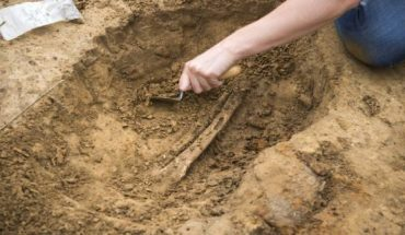 One of the human leg bones being excavated at Mont‐Saint‐Jean site. (Photo by Chris van Houts)