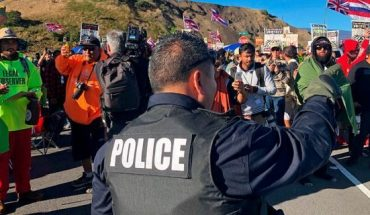 A police officer gestures at demonstrators blocking a road at the base of Hawaii