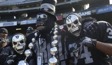 FILE - In this Sept. 29, 2013, file photo, Oakland Raiders fan Gorilla Rilla, center, poses for photographs with fans before an NFL football game between the Oakland Raiders and the Washington Redskins in Oakland, Calif. The Raiders