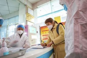 Medical workers in protective gear talk with a woman suspected of being ill with a coronavirus at a community health station in Wuhan in central China
