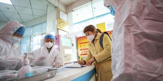 Medical workers in protective gear talk with a woman suspected of being ill with a coronavirus at a community health station in Wuhan in central China's Hubei Province on Monday. (Chinatopix via AP)
