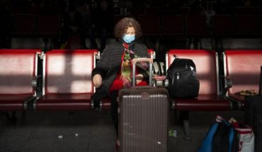 A traveler wears a face mask as she sits in a waiting room at Beijing West Railway Station in Beijing.