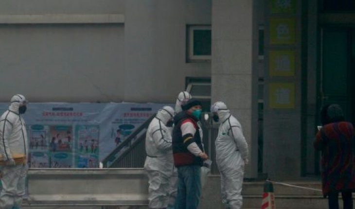 Staff in biohazard suits hold a metal stretcher by the in-patient department of Wuhan Medical Treatment Center, where some infected with a novel coronavirus are being treated, in Wuhan, China, on Tuesday. Heightened precautions were being taken in China and elsewhere Tuesday as governments strove to control the outbreak of the coronavirus, which threatens to grow during the Lunar New Year travel rush. (AP Photo/Dake Kang)