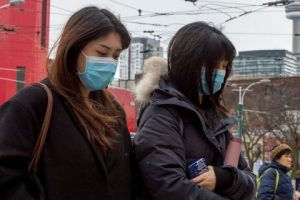 Pedestrians wear protective masks as they walk in Toronto on Monday. Canada