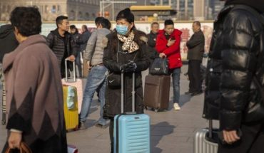 A traveler wears a face mask as she stands near the Beijing Railway Station in Beijing.