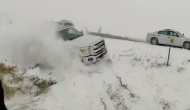 Video released by the Iowa State Patrol shows a state trooper and another man nearly getting hit by a vehicle that lost control on a snowy highway.