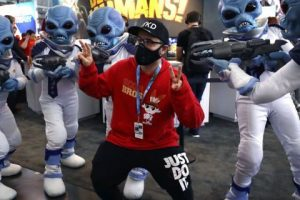 "Eric Vita, of Morris Plains, N.J., center, wears a protective mask while posing for a photograph with people dressed as ""Crypto,"" the main character in the video game ""Destroy All Humans!,"" Thursday, Feb. 27, 2020, at the Pax East conference, in Boston. Vita said concerns about the coronavirus played a role in his decision to wear a mask to the conference. (AP Photo/Steven Senne)"