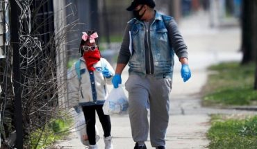Erica Harris, right, and her daughter Jordan, wear their protective masks as they walk back home after getting a lunch and homework from the child's school on Chicago's Southside in Chicago.